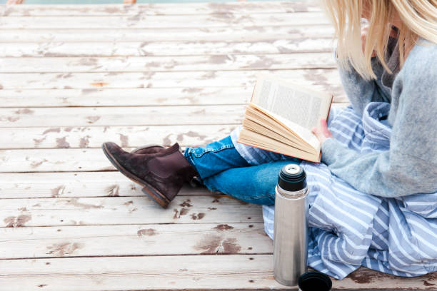Woman is reading book on wooden pier on autumn beach. Cozy fall picnic with coffee, hot beverages, tea stock photo
