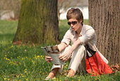 woman is reading magazine in the park