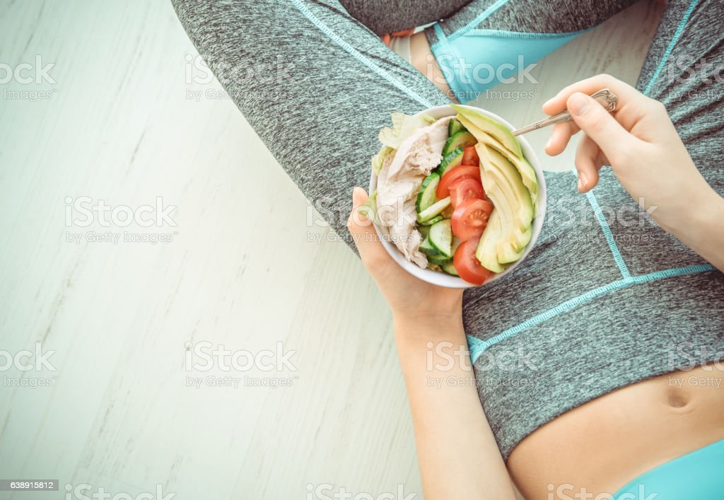 Woman is resting and eating a healthy salad . stock photo