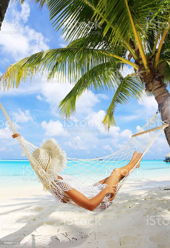 Woman is resting in hammock near the sea. stock photo