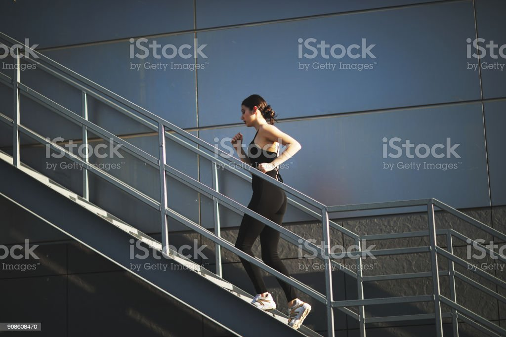 Woman is runing on the city stairs stock photo