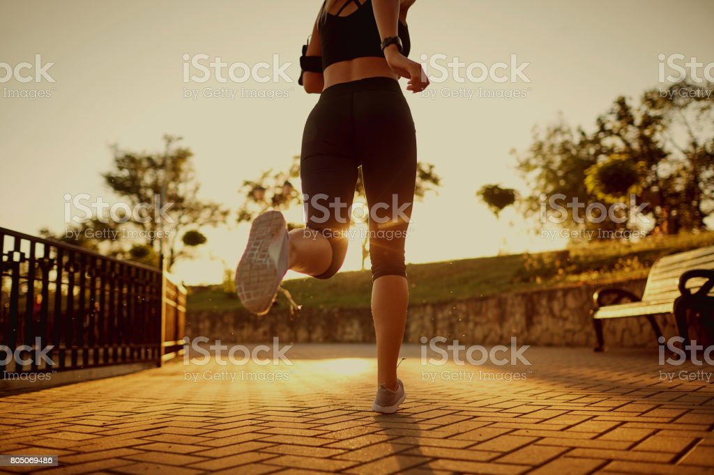 A woman is running along the road in the park. stock photo