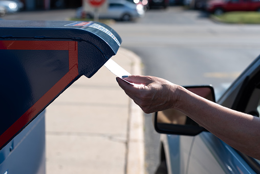 Palatine, IL/USA - 08-27-2020:  Safely mailing an application for ballot for 2020 election at a  drive-up mailbox at the US Post Office