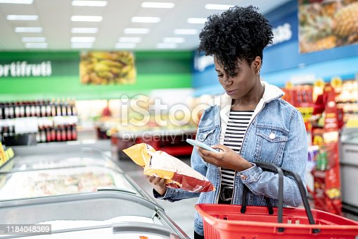 1184048369 istock photo Woman is shopping in supermarket and scanning barcode with smartphone 1184048369