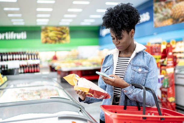 woman is shopping in supermarket and scanning barcode with smartphone - icona supermercato foto e immagini stock