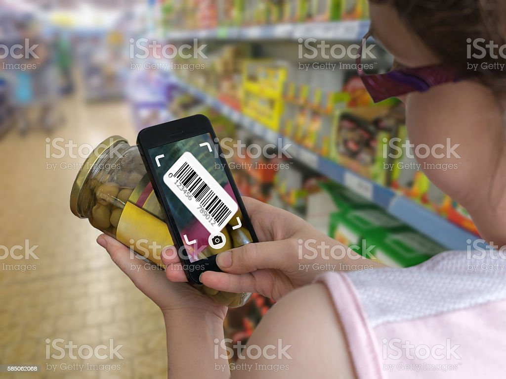 Woman is shopping in supermarket and scanning barcode with smartphone. stock photo