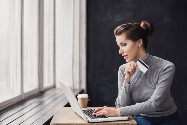 woman is shopping online with laptop computer and credit card - business credit card stock photos and pictures