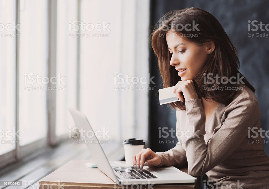 Woman is shopping online with laptop bildbanksfoto