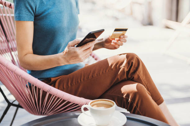 Woman is shopping online with smartphone and credit card stock photo