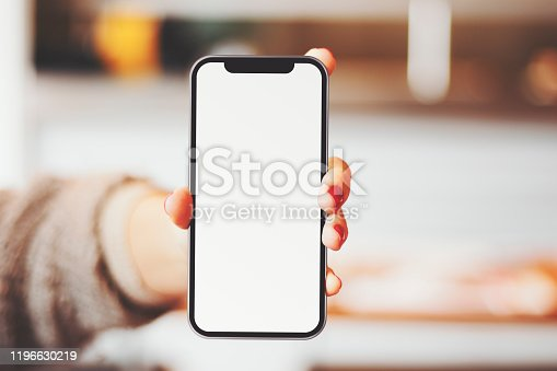 Woman is showing her mobile phone in her hand. Horizontal composition with copy space.
