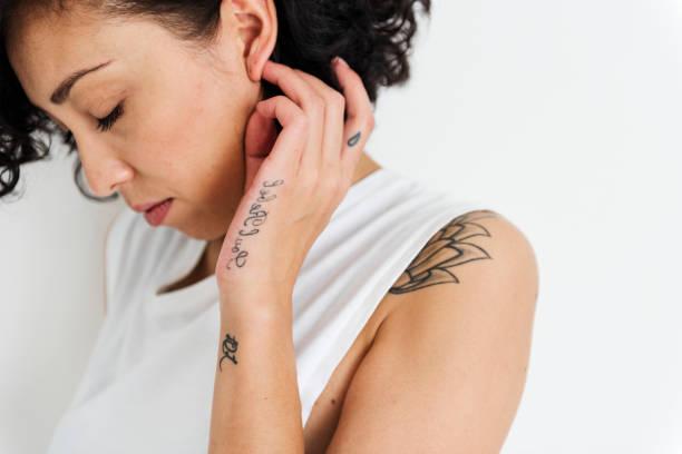 eine frau zeigt ihr tattoo auf ihren körper - tatto vorlagen stock-fotos und bilder