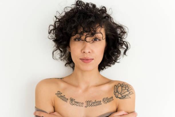 eine frau zeigt ihr tattoo auf der brust - tatto vorlagen stock-fotos und bilder
