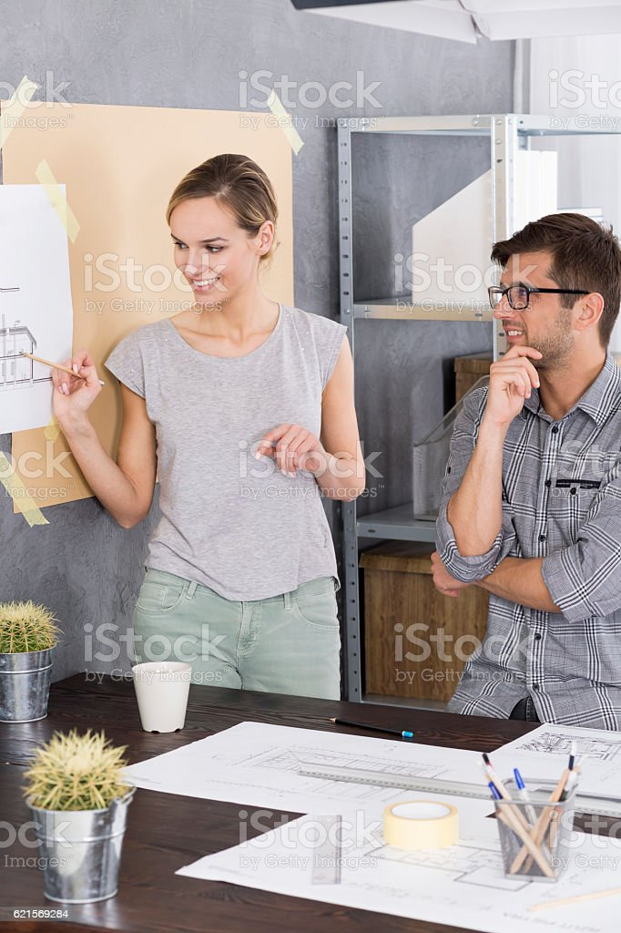 Woman is showing something on a drawing foto stock royalty-free