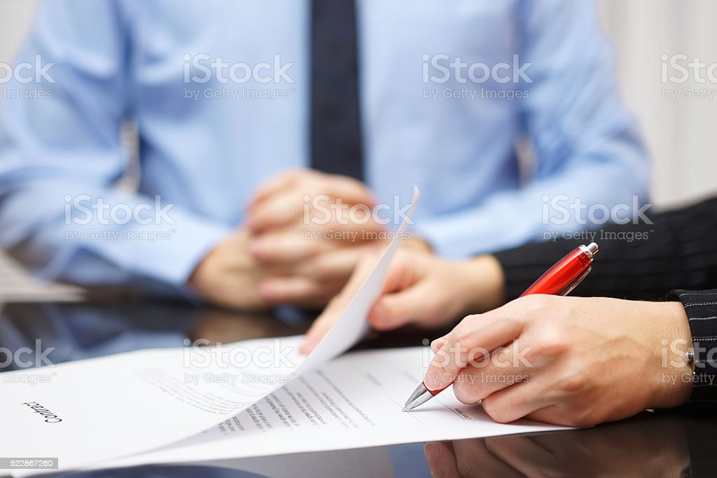 Mulher assinatura contrato de homem de negócios em plano de fundo - foto de acervo