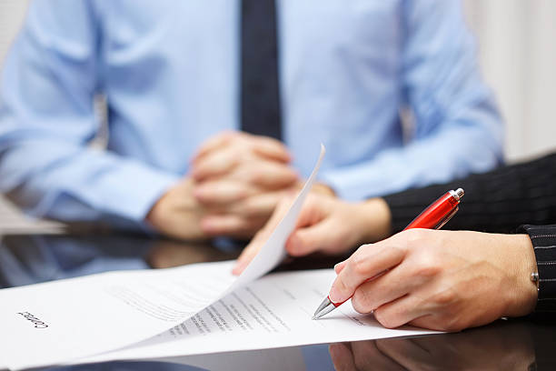 woman is signing contract with business man in background stock photo