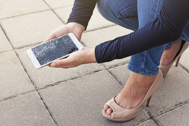 Woman is sitting and holding a broken smart phone with a cracked screen stock photo
