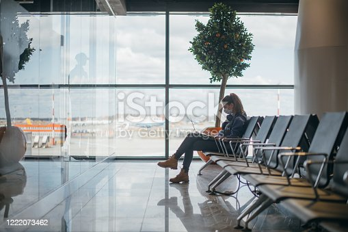 A woman is sitting at the airport with a laptop in a medical mask. A young girl is waiting for departure at the gate, working online. Social responsibility, virus protection.