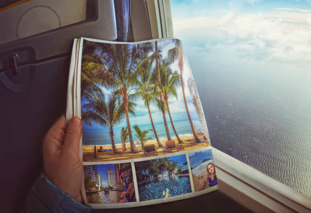 Woman is sitting   by window on a plane with magazine in hands stock photo