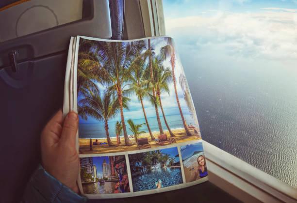 vrouw zit door raam op een vliegtuig met magazine in handen - newspaper beach stockfoto's en -beelden