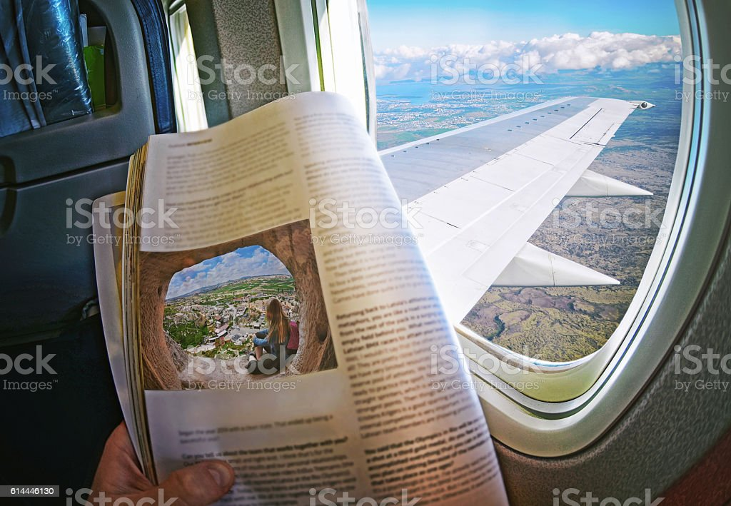 Woman is sitting   by window on a plane with magazine stock photo