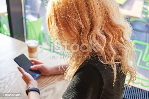 A blonde woman is sitting in a cafe with a cup of cappuccino and is using a smartphone.
