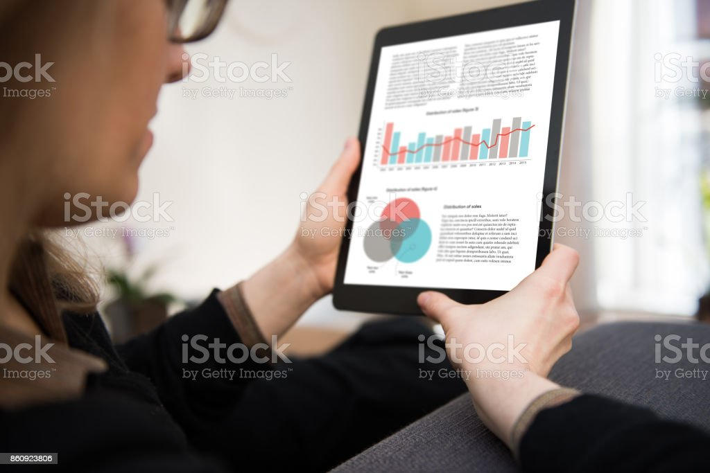 Woman is sitting in a living room looking at a tablet computer showing data, statistics and graphs. stock photo