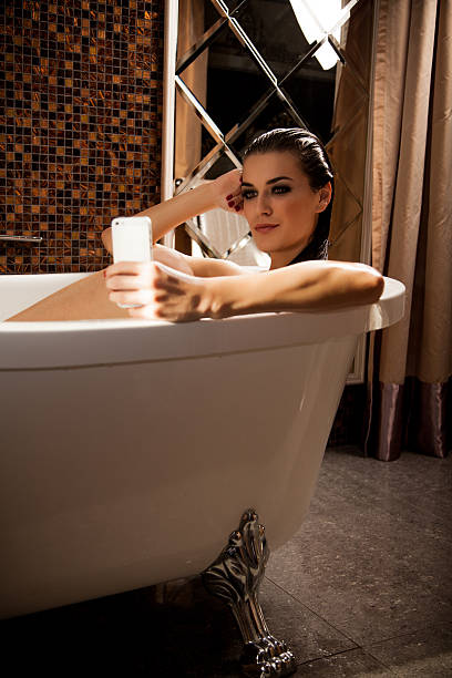 Woman is sitting in bath and have videochat by smartphone stock photo