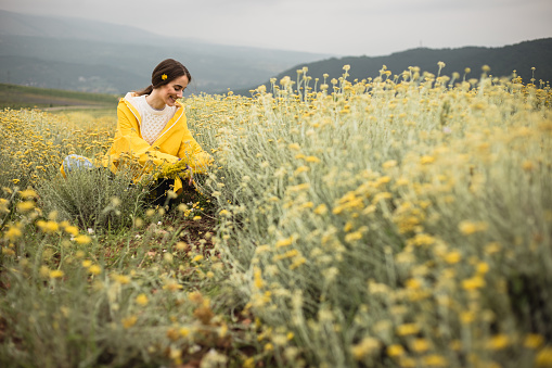 Woman is sitting in herb field and enjoying nature