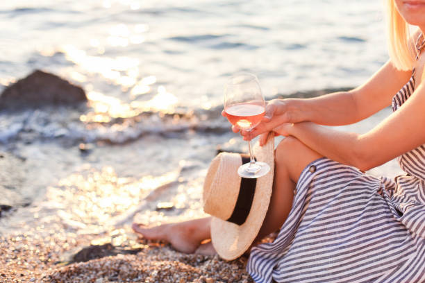 Woman is sitting on sea beach with wineglass of pink wine at sunset in summer vacation in resort. Tourist girl in striped dress with straw hat is enjoying life, relaxing, drinking, traveling. stock photo