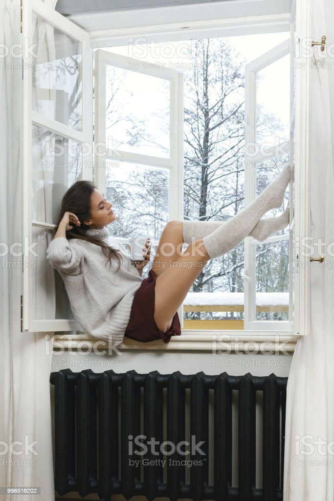 Woman Is Sitting On The Windowsill And Drinking Hot Tea Or Coffee