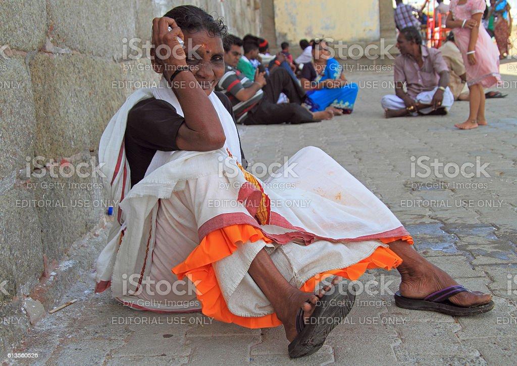 woman is sitting outdoor in Kanyakumari, India stock photo