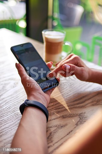 A woman is sitting in a cafe with a cup of cappuccino and using a smartphone.