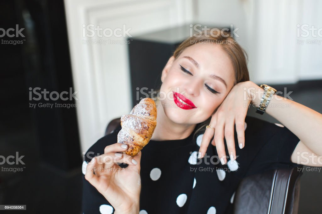 A woman is sniffing a freshly baked croissant stock photo