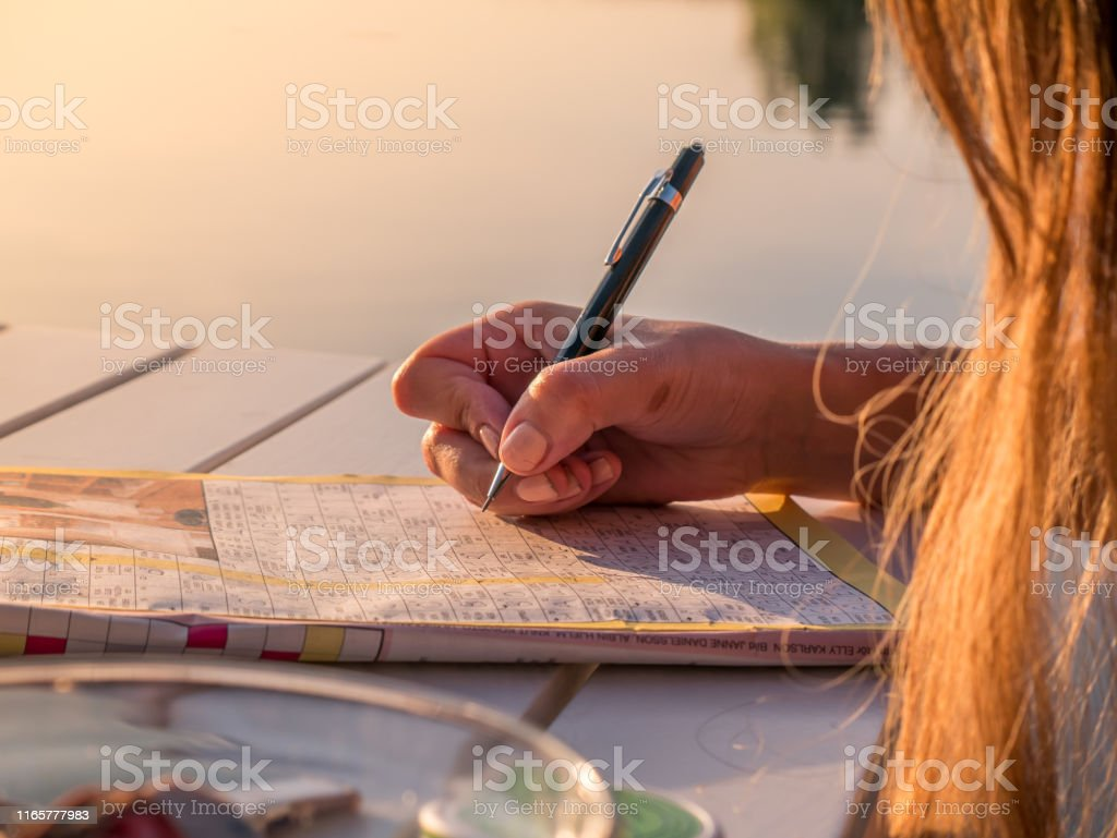 Woman is solving a crossword puzzle paper. Calm summer holiday activity. Woman is solving a crossword puzzle paper. Calm summer holiday activity. Adult Stock Photo