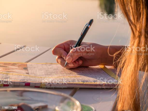 Woman Is Solving A Crossword Puzzle Paper Calm Summer Holiday Activity Stock Photo - Download Image Now