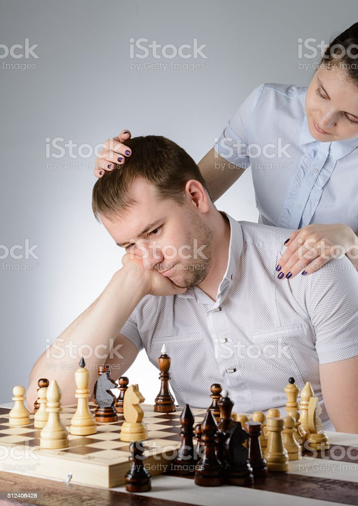 Woman is standing behind man and pats on the head stock photo