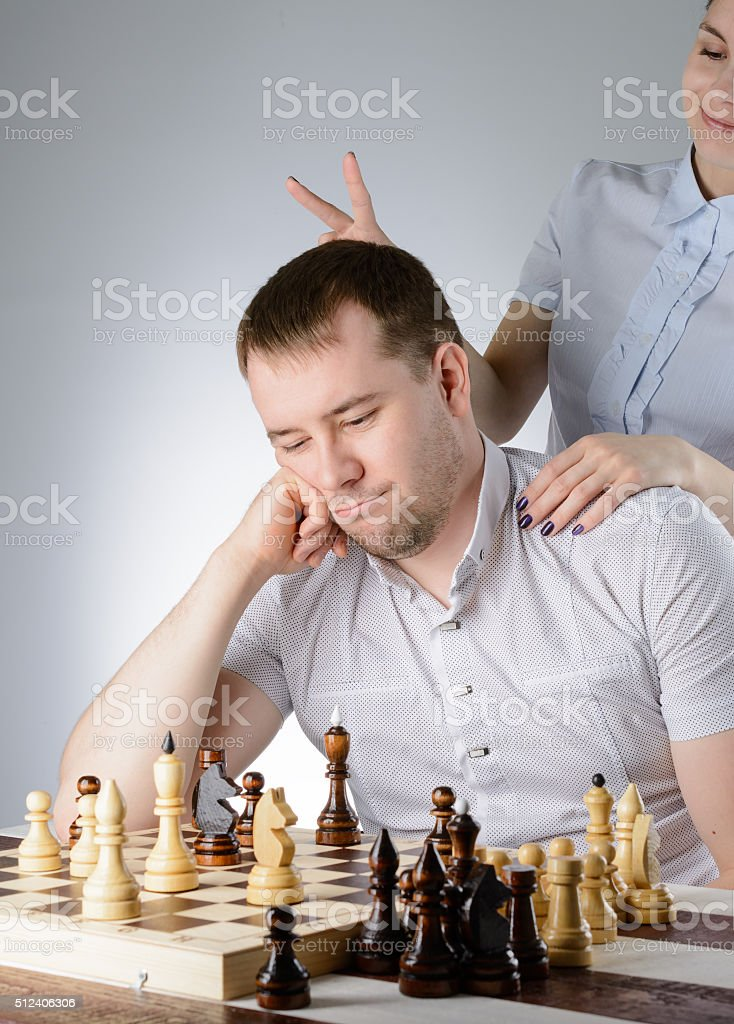 Woman is standing behind the man and put horns stock photo