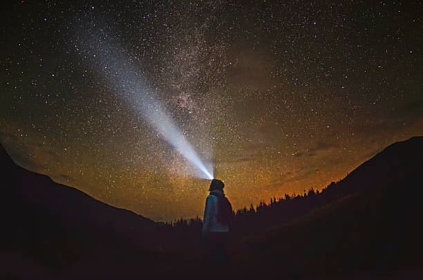 Woman is standing in the forest and pointing the Milky Way stock photo