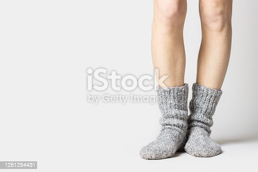 istock Woman is standing in warm gray socks on a light background. Only legs visible. Banner 1251254431
