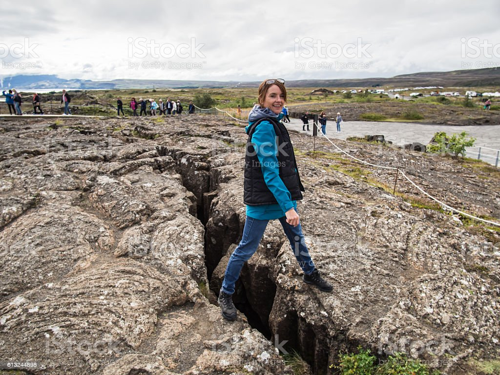 Woman is standing on an earth gap at Thingvellir stock photo