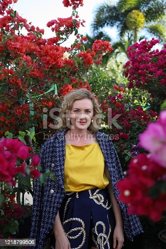 Blond beautiful woman in is standing on front on bougainvillea bush