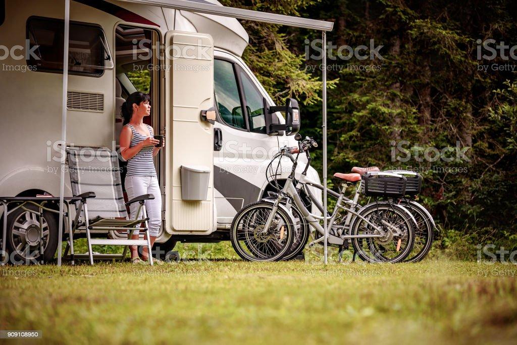 Frau steht mit einer Tasse Kaffee in der Nähe der Camper RV – Foto