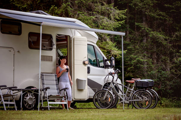 Woman is standing with a mug of coffee near the camper RV. Woman is standing with a mug of coffee near the camper. Caravan car Vacation. Family vacation travel, holiday trip in motorhome RV rv bike stock pictures, royalty-free photos & images