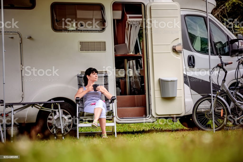 Woman is standing with a mug of coffee near the camper RV. stock photo