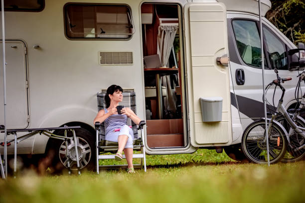 woman is standing with a mug of coffee near the camper rv. - motorhome stock photos and pictures