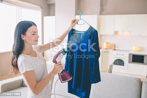 524159504 istock photo Woman is steaming blue shirt in room. She holds small stream iron in hand. Brunette is concentrated on work. 1144511966
