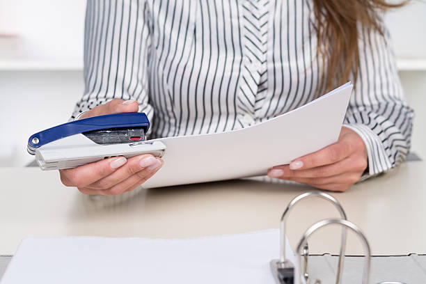 Woman is stitching documents together A businesswoman is stitching documents together at the desk in the office. stapler stock pictures, royalty-free photos & images