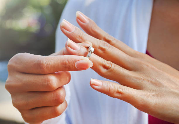 Woman is taking off the wedding ring stock photo
