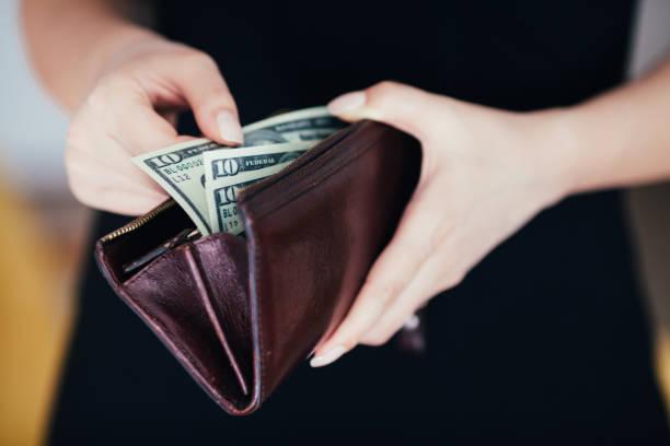 frau nimmt geld aus der brieftasche - inflation stock-fotos und bilder