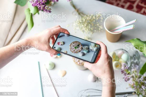 Photo of A woman is taking photos on a mobile phone camera of a whipped morning Dalgona coffee. White background, pastel colors and lilac flowers